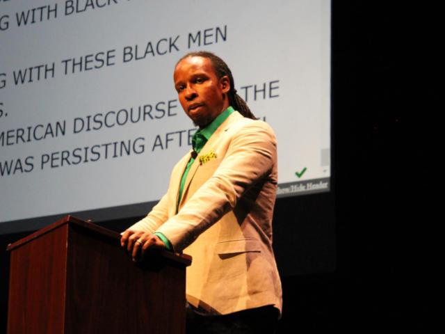 Ibram X. Kendi speaking at a podium at Zellerbach Hall at UC Berkeley