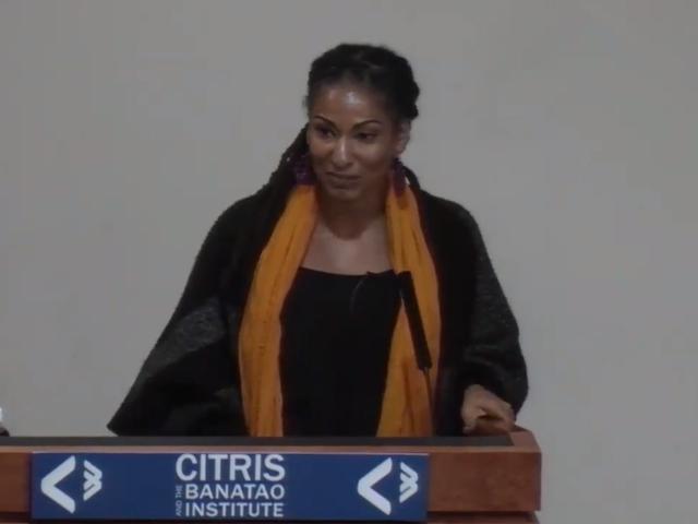 Ruha Benjamin speaking at a podium